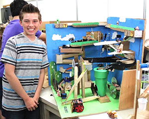 This high school freshman stands proudly by his Rube Goldberg project.