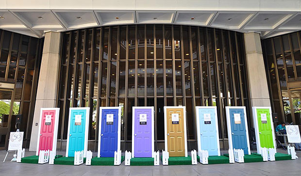 doors of different colors lined up as to welcome you