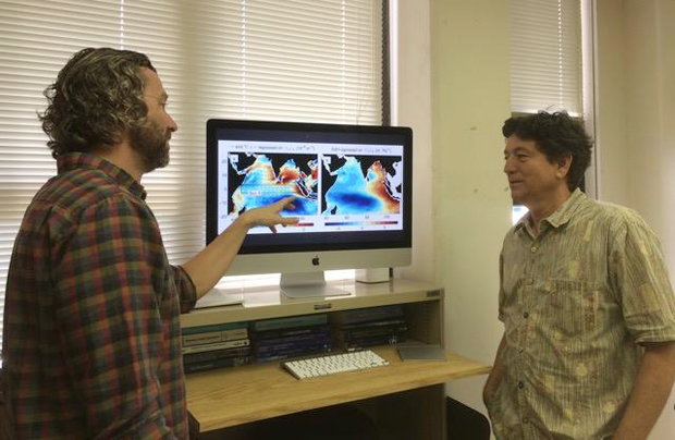 Two researchers looking at data on a computer screen