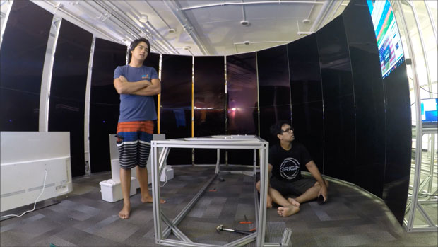 One student standing and one sitting in the CyberCANOE during the building process