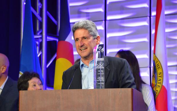 David Lassner at a podium with an award