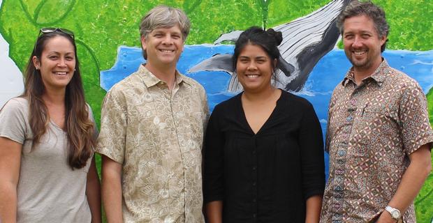four people standing in front of ocean mural