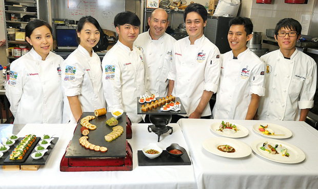 7 people wearing chef uniform standing behind culinary dishes