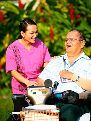 Student assisting smiling resident in wheel chair