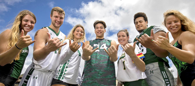 students in athletic attire smiling and giving the shaka hand sign
