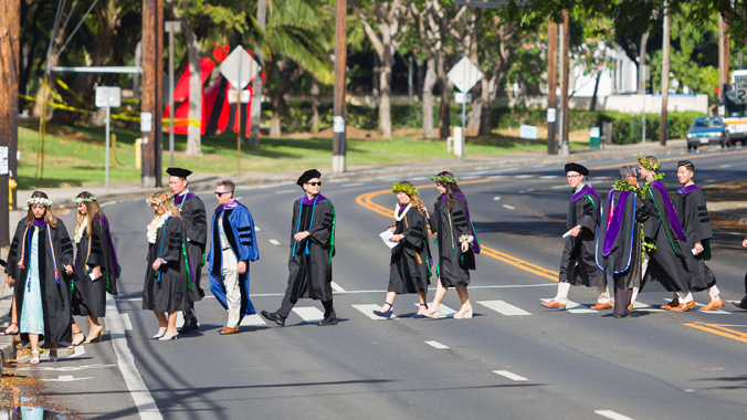law school graduates in cap and gowns crossing street