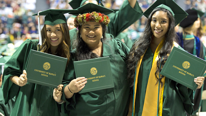 3 University of Hawaii at Manoa graduates in cap and gown