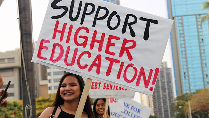 Rovy Dipaysa holding a sign to Support Higher Education