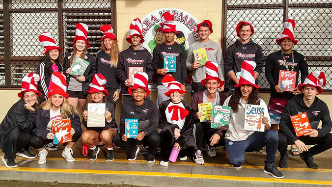 U H Hilo students in Dr. Seuss hats holding books