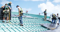 workers installing photovoltaic system on roof