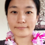 Photo of student Wenyi Ling with lei on