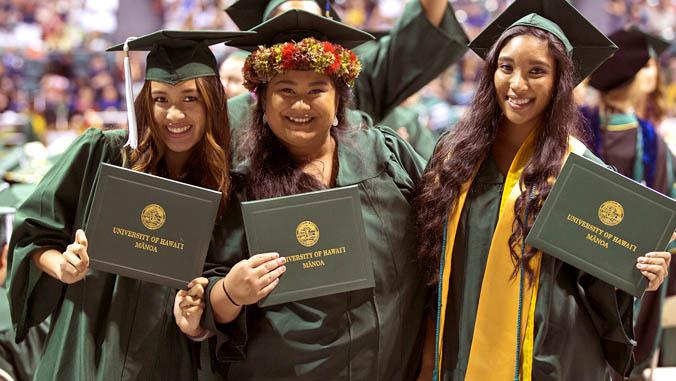 smiling female graduates holding diplomas