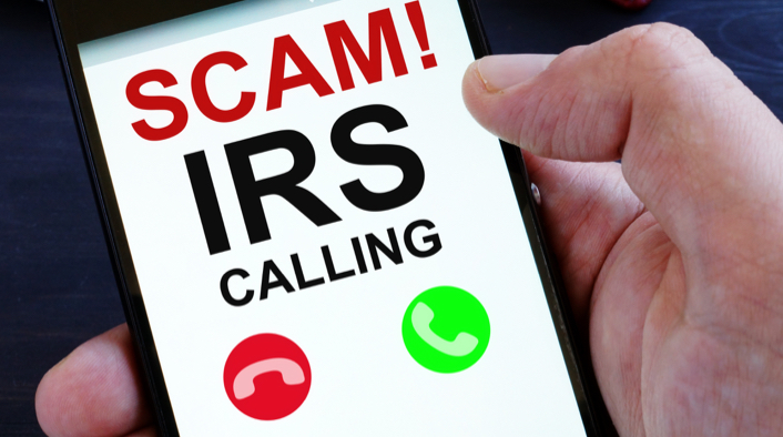 mobile phone displaying SCAM! IRS CALLING