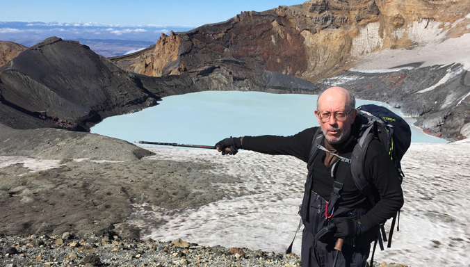 Houghton pointing a stick at a water-filled crater