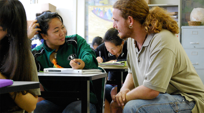 Teacher talking with a student in a classroom
