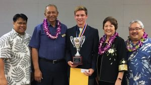 student holding science fair trophy with four other people