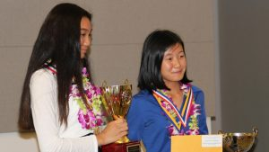 science fair winner holding trophy
