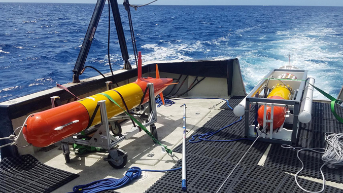 torpedo-like robot on deck of ship out at sea