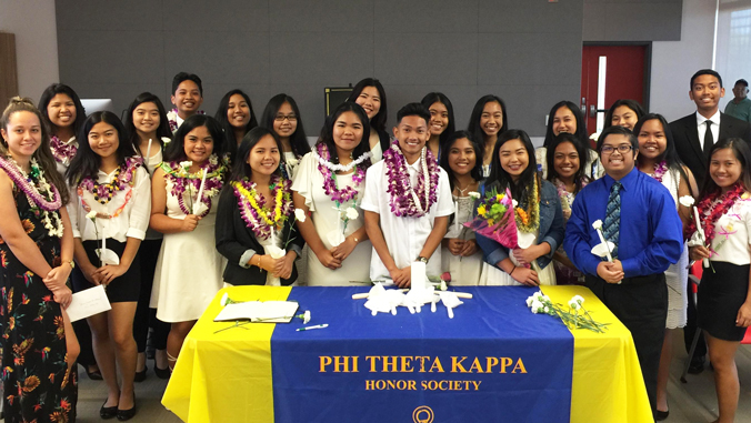 Large group of Phi Theta Kappa inductees standing behind a table