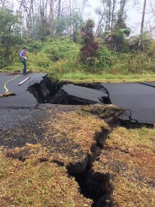 Person standing on one side of a huge crack in the road