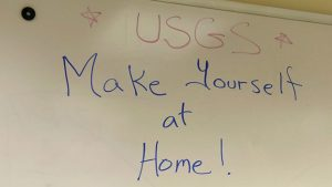 Sign on whiteboard: U S G S make yourself at home!