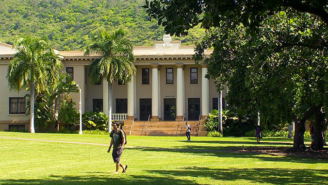 Student walking on the lawn in front of Hawaii Hall
