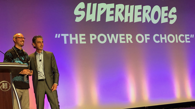 """two people standing on a stage with the word Superheroes """"The Power of Choice"""" behind them"""