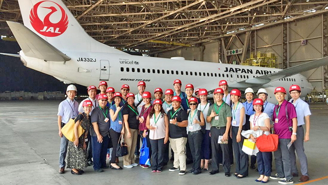 large group of people wearing red caps standing in front of a Japan Airlines plane