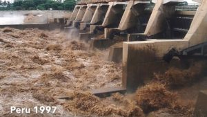 brown water pouring out of dam