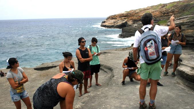 students and teacher near ocean