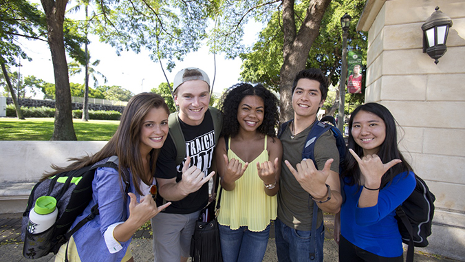 Smiling students flashing shaka