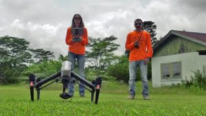 Two people in a field with a drone. Click image for larger version