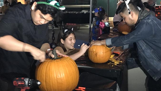 U H students carving pumpkins