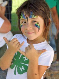 girl with face painted wearing 4-H shirt and waving shaka