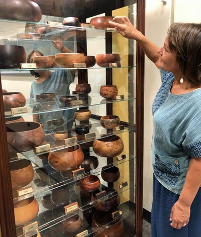 women putting bowl into bowl display case