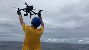 Man releasing a drone at sea