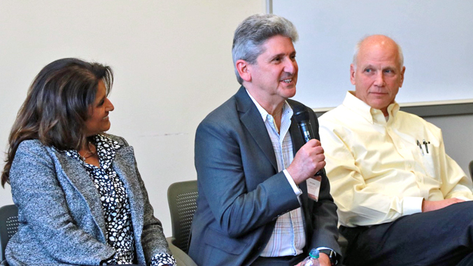 three people sitting and one person holding a microphone talking