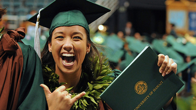 Smiling woman holding diploma and flashing a shaka