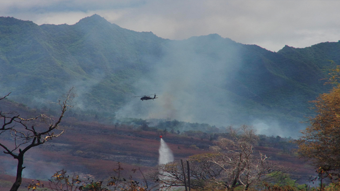 helicopter dropping water on wildfire in Hawaii