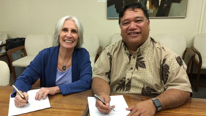 Two people signing papers