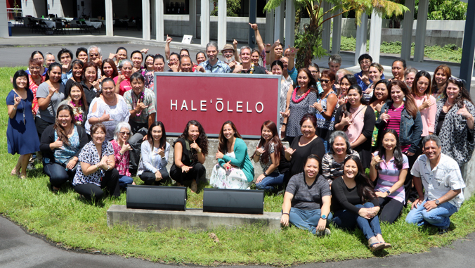 large group of people around Hale Oolelo sign