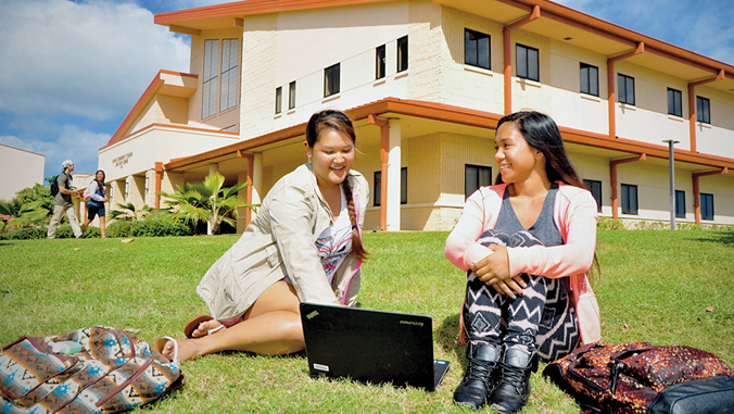 students sitting in front of Kauai C C building