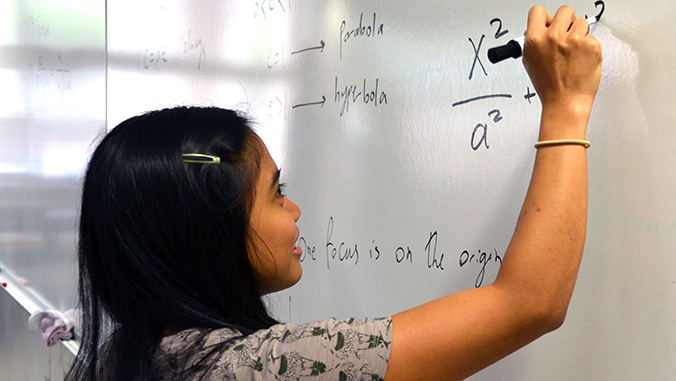 Student writing on a whiteboard