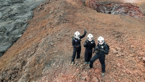 Researcher in space suits waving to drone flying above them