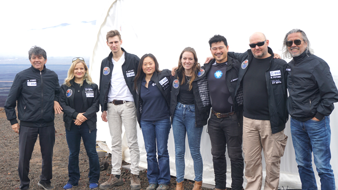 8 people standing in front of white dome on Mauna Loa