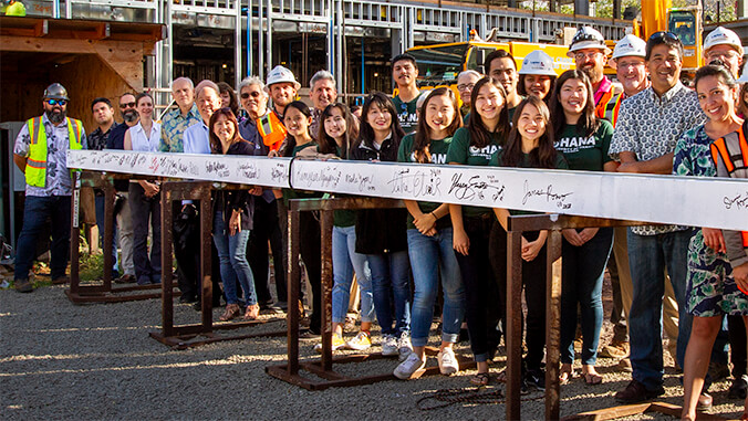 large group of people smiling and standing behind the signed steel beam