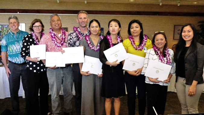 group of people holding certificates