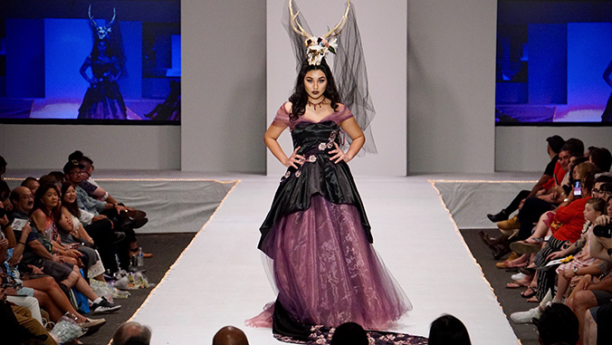 Model in a black and mauve dress with animal skull headdress