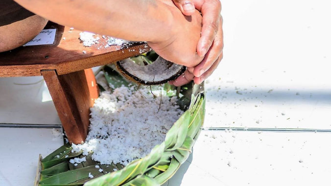 Photo of hands scraping a coconut.