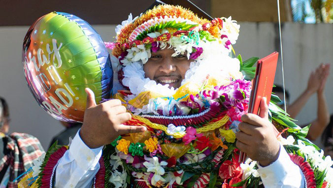 guy wearing lei's at commencement